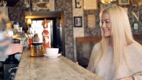 Une jeune belle femme paye son thé avec un smartphone et remercie le serveur 4K banque de vidéos