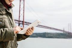 Une jeune belle femme utilise un comprimé pour communiquer avec des amis ou regarde une carte ou un autre chose Pont 25 avril photo libre de droits