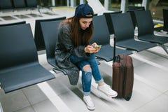 Une jeune belle fille dans le style occasionnel avec une valise s'assied dans la salle d'attente d'aéroport et utilise un télépho Photographie stock libre de droits