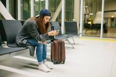 Une jeune belle fille dans le style occasionnel avec une valise s'assied dans la salle d'attente d'aéroport et utilise un télépho Image stock
