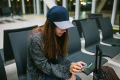 Une jeune belle fille dans le style occasionnel avec une valise s'assied dans la salle d'attente d'aéroport et utilise un télépho Photos stock