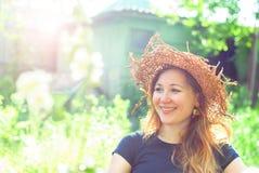 Une jeune belle fille dans un chapeau de paille sourit au soleil Photographie stock
