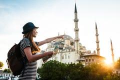 Une jeune belle fille de voyageur dans un chapeau avec un sac à dos et une carte à côté de la mosquée bleue est une vue célèbre à Images stock