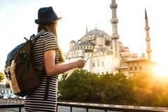 Une jeune belle fille de voyageur dans un chapeau avec un sac à dos observe une carte à côté de la mosquée bleue - la vue célèbre Image stock