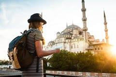 Une jeune belle fille de voyageur dans un chapeau avec un sac à dos observe une carte à côté de la mosquée bleue - la vue célèbre Images stock