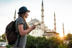Une jeune belle fille de voyageur dans un chapeau avec un sac à dos observe une carte à côté de la mosquée bleue - la vue célèbre Photo libre de droits