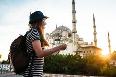 Une jeune belle fille de voyageur dans un chapeau avec un sac à dos observe une carte à côté de la mosquée bleue - la vue célèbre Images libres de droits
