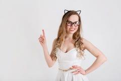 Une jeune belle fille en robe blanche et verres demande l'attention photo stock