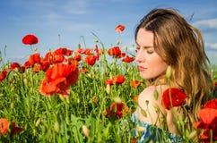 Une jeune belle fille gaie marche dans un pré de pavot parmi les pavots de floraison de rouge un jour lumineux, chaud, ensoleillé Photographie stock libre de droits