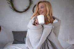 Une jeune belle fille s'asseyant dans le lit dans une bâche froide de jour avec la couverture et le thé potable, regard et sourir image libre de droits