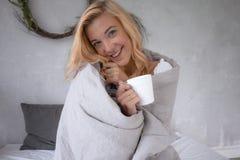 Une jeune belle fille s'asseyant dans le lit dans une bâche froide de jour avec la couverture et le thé potable, regardant et sou images stock