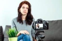 Une jeune belle fille s'assied devant un DSLR et un a de enregistrement Vlog, plan rapproch? Blogger, bloguant, technologie, arge photographie stock libre de droits