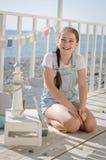 Une jeune belle fille s'assied sur la plage garde des jouets et le sourire Images stock
