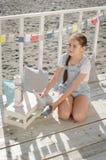 Une jeune belle fille s'assied sur la plage garde des jouets et le sourire Photo stock