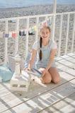 Une jeune belle fille s'assied sur la plage garde des jouets et le sourire Photographie stock