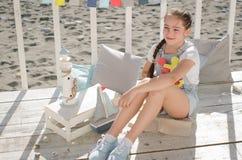 Une jeune belle fille s'assied sur la plage garde des jouets et le sourire Photos stock