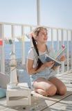 Une jeune belle fille s'assied sur la plage garde des jouets et le sourire image libre de droits
