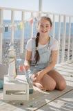 Une jeune belle fille s'assied sur la plage garde des jouets et le sourire Images libres de droits