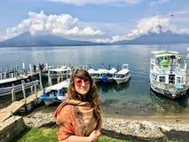 Une jeune belle position de touristes aux rivages du lac Atitlan, avec la beaux eau et volcans calmes à l'arrière-plan image stock