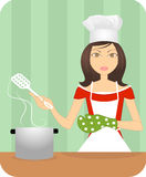 Une jeune dame attirante faisant cuire dans la cuisine Photographie stock libre de droits