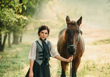 Une jeune dame dans une robe de vintage flâne par la forêt avec son cheval La fille a un chemisier blanc, un jabot, un lien photos stock
