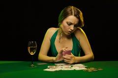 Une jeune dame dans une robe verte joue le solitaire fait ? partir des cartes scrying photo stock