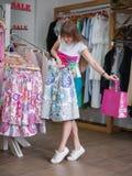 Une jeune dame gaie se tenant dans le magasin d'habillement et se choisissant une jupe colorée Un shopaholic sur brouillé images libres de droits