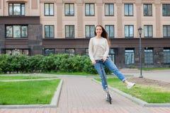 Une jeune et attirante fille avec de longs cheveux bruns dans un chandail léger montant un scooter dans un nouveau complexe résid Photo stock