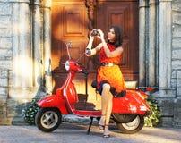 Une jeune et heureuse brune sur un vieux scooter rouge Photographie stock