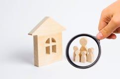 Une jeune famille avec des enfants se tient près d'une maison en bois Th Photographie stock libre de droits