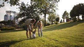 Une jeune famille avec un bébé marchant en parc sur l'herbe banque de vidéos