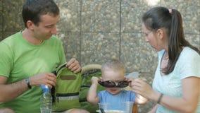 Une jeune famille avec un enfant mesure des lunettes de soleil sur un bébé Le papa et le bébé de maman s'asseyent dans le café de banque de vidéos