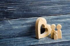 Une jeune famille avec un enfant se tient près d'un coeur en bois Amour et fidélité, une jeune famille forte Liens de parenté Images libres de droits