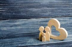 Une jeune famille avec un enfant se tient près d'un coeur en bois Amour et fidélité, une jeune famille forte Liens de parenté Image libre de droits