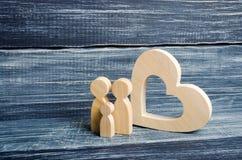 Une jeune famille avec un enfant se tient près d'un coeur en bois Amour et fidélité, une jeune famille forte Liens de parenté civ Images libres de droits