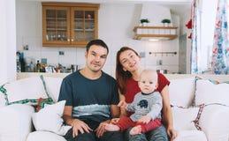 Une jeune famille espiègle à la maison sur le divan Images libres de droits