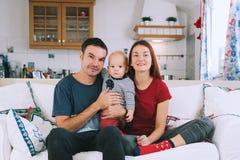 Une jeune famille espiègle à la maison sur le divan Photos stock