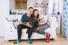 Une jeune famille espiègle à la maison sur le divan Images stock