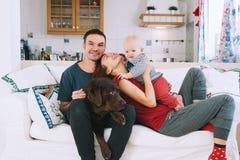 Une jeune famille espiègle à la maison sur le divan Image libre de droits