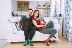 Une jeune famille espiègle à la maison sur le divan Photo libre de droits