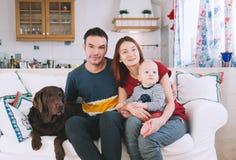Une jeune famille espiègle à la maison sur le divan Photographie stock