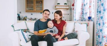 Une jeune famille espiègle à la maison sur le divan Photos libres de droits