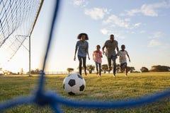 Une jeune famille noire courant après un football pendant un jeu images stock