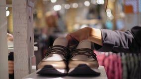 Une jeune femelle choisit de nouvelles espadrilles dans le magasin Photo stock