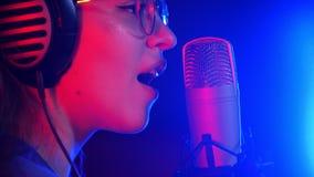 Une jeune femme émotive dans des écouteurs chantant dans le studio Éclairage au néon banque de vidéos