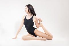 Une jeune femme, étirant la jambe, maillot de bain se reposant photo stock