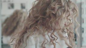 Une jeune femme après un coiffeur admire une nouvelle coiffure banque de vidéos