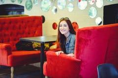 Une jeune femme arabe d'aspect sur un sofa rouge dans un café piaulant Photographie stock libre de droits