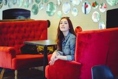 Une jeune femme arabe d'aspect sur un sofa rouge dans un café piaulant Photos libres de droits