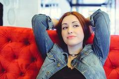 Une jeune femme arabe d'aspect sur un sofa rouge dans un café piaulant Images libres de droits